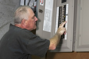 Man checking the electrical breakers in the fusebox